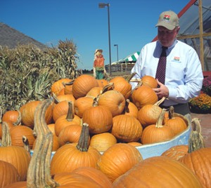 Photo of Secretary Kuperus admiring the pumpkins and Johnsons Farm