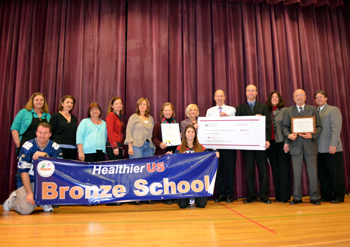 Photo of state, county and school officials displaying the Healthier US School Challenge Awards
