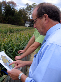 Photo of Secretary Fisher looking at the corn maze map