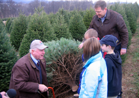 Photo of Secretary Kuperus, Assemblyman Doherty and Wyckoff children cutting a Christmas tree - Click to enlarge