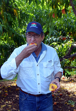 Photo of Secretary Fisher enjoying a Jersey peach