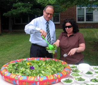 Photo of Secretary Fisher and parent volunteer serving at Salad Extravaganza