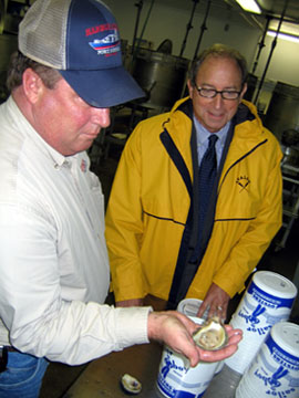 Photo of Todd Reeves and Secretary Fisher with shucked oyster