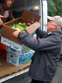 Photo of Secretary Kuperus loading donated produce onto a food pantry truck