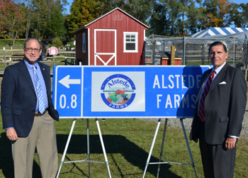 Photo of Secretary Fisher and Deputy DOT Commissioner Mrozek with an example of a TODS sign