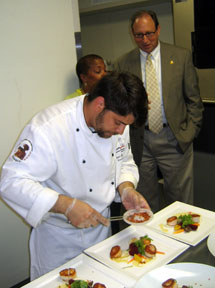 Photo of Fischbach and Secretary Fisher preparing scallops dishes