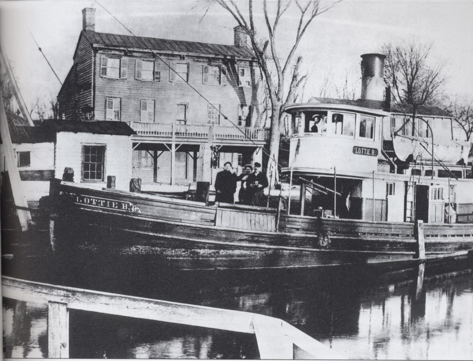 "The steam tug Lottie B is seen towing a canalboat toward New Brunswick near the Railroad Hotel along Alexander Road in Princeton.  The hotel, later named the ""Steamboat Hotel"" when the railroad was relocated to Princeton Junction, served canal workers and merchants conducting business at the factories and establishments of the nearby Princeton Basin."