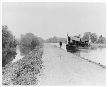 Mr. George Holcombe, Paymaster of the Delaware and Raritan Canal Company, stands next to the steam yacht Relief in this photograph taken north of the City of Lambertville in the year 1892.   Constructed in Camden and launched in 1884, the Relief was used by the Delaware and Raritan Canal Company as a pay-boat and traveled the length of the canal monthly to disburse wages to company workers.