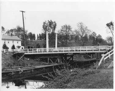 "This photograph provides a detailed view of the design of the King-Post style swing bridge that supplanted the A-Frame bridges along the canal.  Originally, A-Frame swing bridges were constructed over the canal crossings.  However, as automobiles and trucks supplanted horse-drawn wagons, the A-Frame bridges were replaced by the stronger King-Post design.  To operate the span, the bridgetender pushed a 10-foot pole and ""walked"" the bridge, which was balanced on three sets of iron wheels.  The wheels rolled on a circular rail, allowing the bridge to swing to one side of the canal on a turntable.  (Photograph reproduced from the Collection of the Library of Congress)"