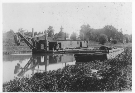 William J. McKelvey noted in his 1975 book that silting from rain and floods was a constant concern on the Delaware and Raritan Canal, and that periodic dredging was required during the years the canal was in operation.  This photograph shows a dredge boat on the Feeder Canal north of the Church Road swing bridge in the Titusville community of Hopewell Township.