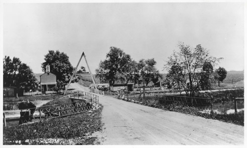This photograph shows Washington Road in Princeton during an era of significantly reduced automobile traffic.  The building on the left is the bridgetender's house, while the small structure on the right is the tender's shelter.    The shelter provided the tender with a warm and dry place to await oncoming vessels.  At each bridge and lock along the Delaware and Raritan canal, the canal company built a home for the tender.  Although many of these buildings were demolished in the decades following the canal's closure, a few of these historically-significant structures remain in places such as Lambertville, Trenton, Kingston, Lawrence, Griggstown, Blackwells Mills, Zarephath, and East Millstone.