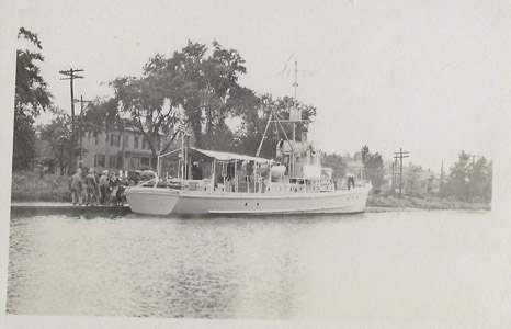 United States Submarine Chaser No. 252 is shown possibly at South Bound Brook in the Delaware and Raritan Canal during the First World War.  The SC252 was a SC-1 Class submarine chaser, a large class of anti-submarine vessels designed at the direction of then-Assistant Secretary of the Navy Franklin D. Roosevelt, who ordered the Navy to design a small, wood-constructed, anti-submarine vessel that could be built quickly in civilian boatyards to combat attacks by German U-boats.  Commissioned on March 7, 1918, the SC252 was 110 feet in length and displaced 85 tons.  She was armed with a 76 mm gun, two .30 caliber Colt machine guns and depth charges.  During World War I, the government used the Delaware and Raritan Canal as a safe corridor to transport boilers and naval supplies to the Brooklyn Navy Yard from Philadelphia and Washington, D.C., while the canal itself was guarded by troops at strategic points.