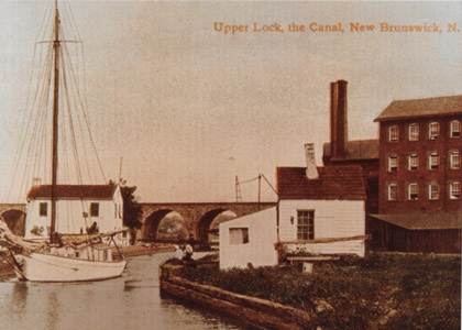 "This colorized 1908 postcard shows a sailboat departing Lock No. 13, known as the ""Deep Lock"" in the City of New Brunswick.   Although not the deepest lock on the Delaware and Raritan Canal (Lock No. 4 south of Lalor Street in Trenton was deeper after it was combined with Lock No. 5 in 1853) Lock No. 13 did raise and lower vessels 12.2 feet.  The locktender's house can be seen behind the boat, while the Johnson & Johnson factory buildings are visible to the right.  Lock No. 13 was filled in order to facilitate the construction of N.J. Highway Route No. 18 through New Brunswick."