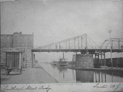 Bridge No. 8 at Southard Street in Trenton is seen in this 1880 photograph.  This bridge was a pivot type swing bridge, which was later replaced by a vertical lift bridge in 1922 that can be seen in Image 37