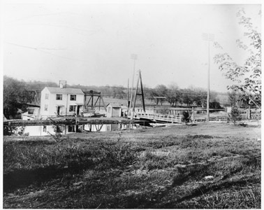 This photograph shows both the Landing Lane swing bridge (Bridge No. 26) over the Delaware and Raritan Canal in New Brunswick, as well as the bridgetender's house and shelter.  Beyond the A-Frame bridge the steel truss bridge which carried traffic over the Raritan River to Piscataway can be seen.  The wooden A-Frame bridge was eventually replaced by the Pennsylvania Railroad during their management of the canal with the cantilevered pony plate girder (inoperative) swing bridge that remains in place to this day.