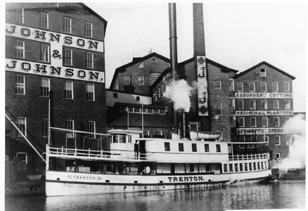 "During the Delaware and Raritan Canal's years of operation, the harbor at New Brunswick was a busy hub of factories, chandleries and shipyards. The pharmaceutical, medical device and consumer products company Johnson & Johnson had its factory adjacent to the canal. Johnson & Johnson also owned its own fleet of boats through a subsidiary company which operated as the ""Middlesex Transportation Company."" Having its own steamboats allowed the company to ensure that it could quickly and reliably transport their products to the docks in New York City. This circa 1902 photograph shows the Trenton loading freight at the factory, which advertised its medical products on the building's exterior walls. The Trenton was constructed in 1859 in Wilmington, Delaware, and operated on the Delaware River and the Delaware and Raritan Canal for 56 years."