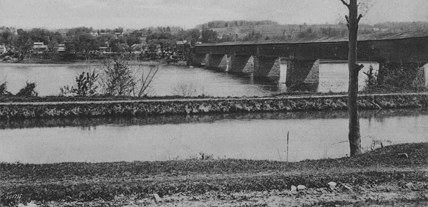 This photograph shows the Delaware and Raritan Feeder Canal in the Borough of Stockton, Hunterdon County, and the Centre Bridge-Stockton covered bridge over the Delaware River.  The covered bridge was destroyed by a fire caused by a lightning strike in 1923.  The current steel truss bridge over the Delaware was constructed in 1927 and rests upon the stone piers that once supported the wooden covered span.  Note the relative absence of vegetation along the canal towpath.  Although the Delaware and Raritan Canal State embankment is heavily-vegetated today, during the canal's period of operation this was not the case.  The Canal Company ensured that the area near the towpath was kept free of trees and plants, which could interfere with boat masts, sails and towlines.