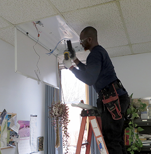 A technician from Tri-State Light and Energy installs new LED lighting in a DRBC office. Photo by DRBC.