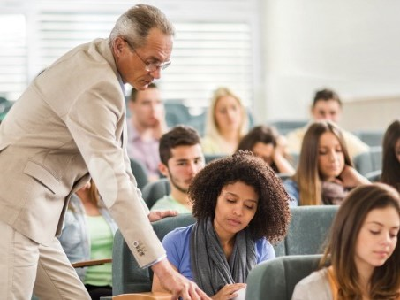 teacher helping college student in lecture hall