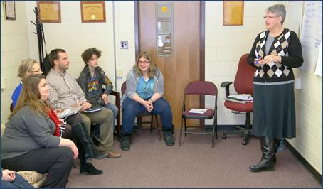 Educator stands facilitating a person centered planning meeting with a student and her supporters sitting semicircularly in chairs.