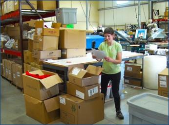Student stands next to cardboard boxes in a warehouse while looking at papers