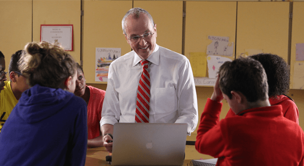 Photo: Phil Murphy behind a laptop talking to kids