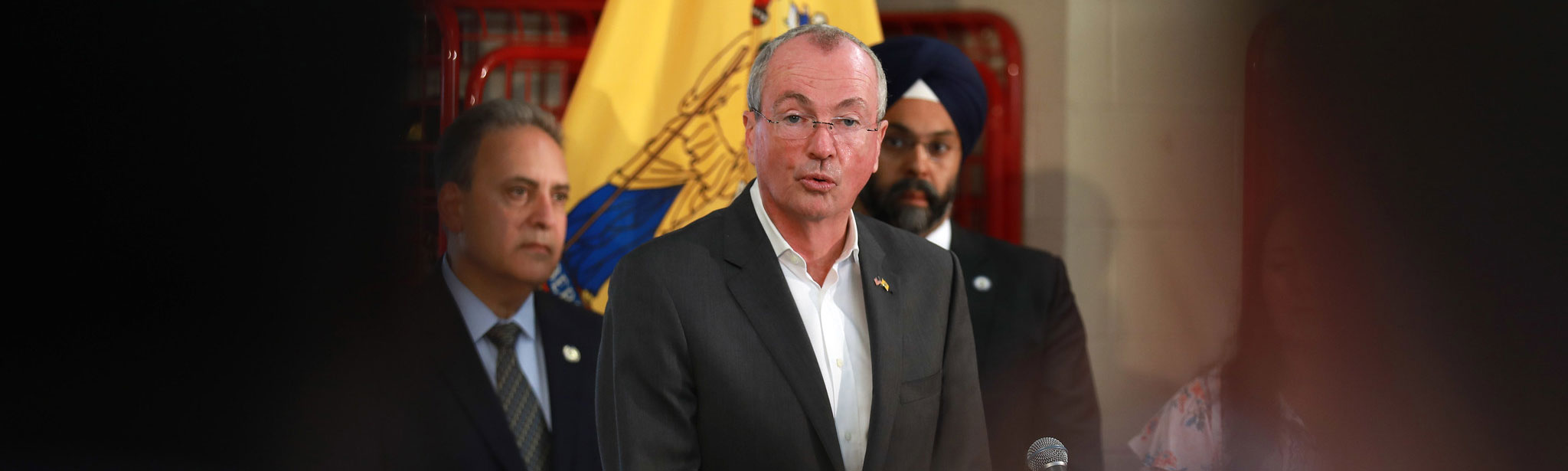 Governor Phil Murphy speakind,  Attorney General Gurbir standing in the background
