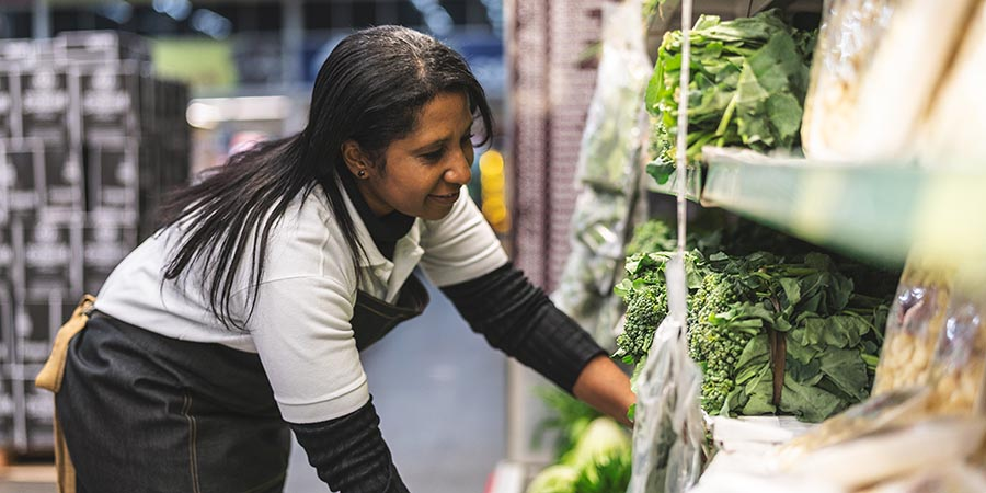 woman stocking produce at a supermarket