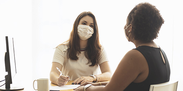 two women in an office at a job interview, wearing masks