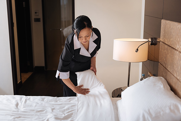 a woman changing the sheets in a hotel room