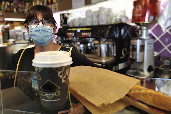 a woman wearing a mask working behind the counter of a cafe