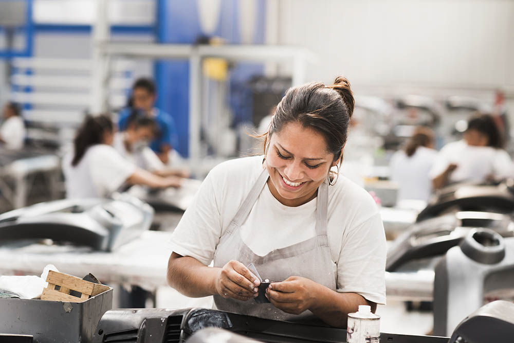 a factory worker smiling as she works