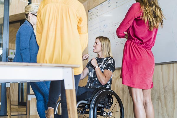coworkers talking in a meeting, including a woman in a wheelchair