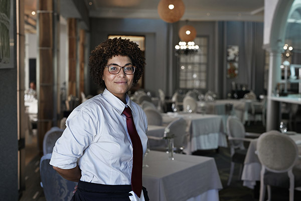 a waitress standing in the dining room of an upscale restaurant