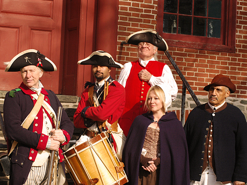 Some of the historical interpreters of the Old Barracks on the steps of the officers' quarters