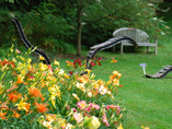 Area containing a bed of flowers and wood sculptures