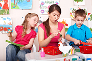 preschool girl and boy with female teacher at crafts table