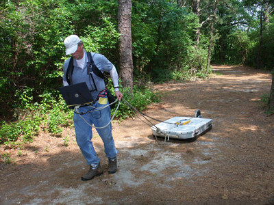 USGS scientist pulling a ground-penetrating radar sled