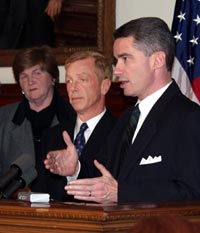 Governor McGreevey (right) presents 'Fix DMV' report at a November 7 news event. With him are DMV Director Diane Legreide and Transportation Commissioner Jamie Fox.
